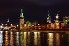 Torres do Kremlin de Moscou com reflexão de incandescência da iluminação da noite na superfície da água do rio de Moskva imagem de stock