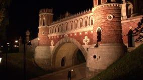 Torres do tijolo vermelho e fortaleza do museu de Tsaritsyno da ponte em Moscou na noite filme