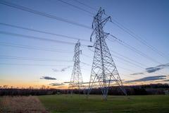 Torres e fios da distribuição da eletricidade no crepúsculo fotografia de stock royalty free