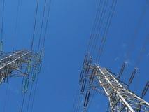 Torres e fios de alta tensão contra o céu azul Fotos de Stock