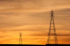 Torres eléctricas de la transmisión en puesta del sol anaranjada Fotos de archivo