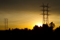 Torres eléctricas de Tranmission contra el cielo de oro Imagen de archivo libre de regalías