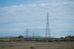 Torres eléctricas sobre campos verdes y un río foto de archivo