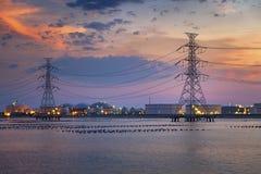 Torres eléctricas y planta refinary del almacenamiento de aceite en crepúsculo imagenes de archivo