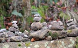Torres empilhadas das pedras e dos seixos na floresta em uma grande rocha fotografia de stock royalty free