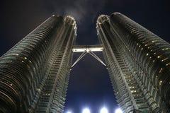 Torres en la noche, Kuala Lumpur de Petronas Imágenes de archivo libres de regalías