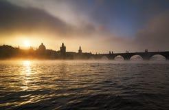 Torres enevoadas da ponte de Charles no rio de Vltava durante o sunr nevoento imagens de stock