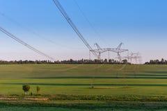Torres enormes de la línea eléctrica en campo en la tarde del verano fotografía de archivo