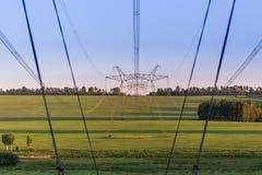Torres enormes de la línea eléctrica en campo en la tarde del verano imágenes de archivo libres de regalías