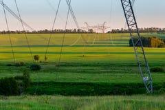 Torres enormes de la línea eléctrica en campo en la tarde del verano imagenes de archivo
