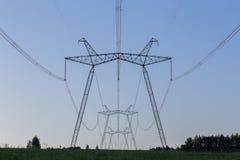 Torres enormes de la línea eléctrica en campo en la tarde del verano fotos de archivo