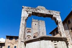 Torres y medieval bien en la cisterna del della de la plaza en San Gimignano en Toscana en Italia Foto de archivo