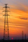 Torretta ad alta tensione del collegare, tramonto Fotografie Stock