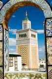 Torretta della moschea - incorniciata con l'arco ornamentale a Tunisi Immagini Stock