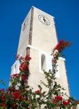 Torretta di orologio circondata dai fiori e dal cielo blu Fotografia Stock