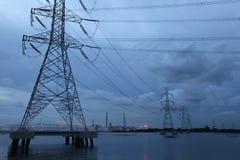 Torretta elettrica sul mare attraverso la proprietà industriale Fotografia Stock Libera da Diritti