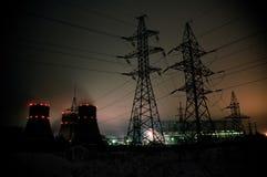 Torri ad alta tensione del trasporto di energia in cielo di tramonto Immagine Stock