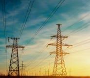 Torri ad alta tensione del trasporto di energia nel fondo del cielo Immagini Stock