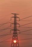 Torri ad alta tensione e tramonto nel concetto di energia Immagine Stock