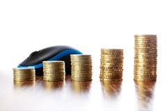 Torri delle monete sulla tavola di legno davanti al topo del computer Immagini Stock
