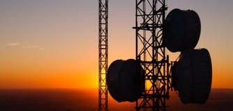Torri di comunicazione cellulari di onda radio che anche orizzonte di tramonto Immagine Stock