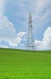 Torri e cavi ad alta tensione nei campi agricoli su un cielo blu Immagini Stock Libere da Diritti