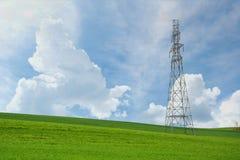 Torri e cavi ad alta tensione nei campi agricoli su un cielo blu Fotografia Stock Libera da Diritti