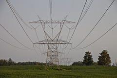 Torri elettriche nel campo verde fertile immagine stock libera da diritti