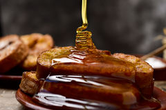 Torrijas, typical spanish dessert for Lent and Easter. Honey dropping on some torrijas, typical spanish dessert for Lent and Easter, served in an earthenware Royalty Free Stock Photography