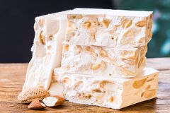 Torrone or nougat. Torrone or nougat with nuts on wood background Royalty Free Stock Images