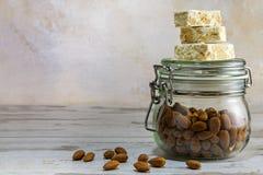 Torrone ou nougat sur un pot en verre avec des amandes sur W rustique lumineux Image stock