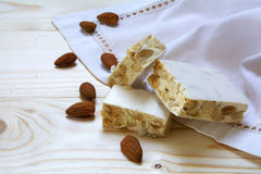 Torrone or white nougat with almonds and napkin on a wooden tab Stock Photo