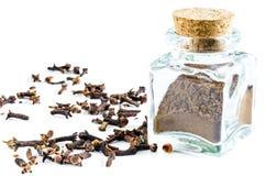 Torrt kryddnejlikapulver i glasflaska och hela kryddnejlikor Arkivbild
