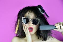 Torrt och skadat hår, orsak för problem för hårförlust av värmehår som utformar hjälpmedelstraighteneren, rolig flicka och dålig  royaltyfria foton