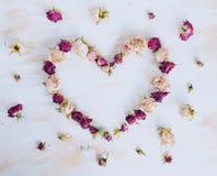 Torrt steg blommor i hjärtaform på gammal träbakgrund Royaltyfri Foto