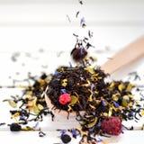 Torrt te med bär och kronblad sliter på tabellen Fotografering för Bildbyråer