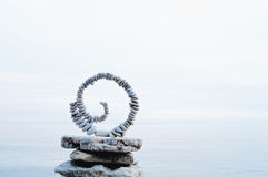 Torsion. White spiral of pebbles on the stack of boulders at the sea royalty free stock images