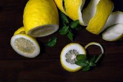 Torsion de peau de citron ou de citron sur un fond en bois de brun foncé avec un brin de parfumé, menthe de vert Des tranches de  Images stock