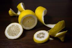 Torsion de peau de citron ou de citron sur un fond en bois de brun foncé Des tranches de citron sont coupées à travers Fin vers l Photographie stock libre de droits