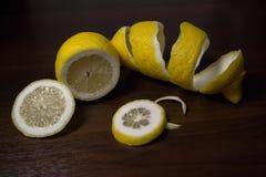 Torsion de peau de citron ou de citron sur un fond en bois de brun foncé Des tranches de citron sont coupées à travers Fin vers l Photos libres de droits