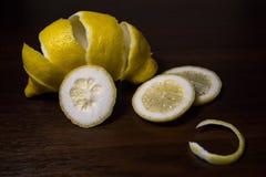 Torsion de peau de citron ou de citron sur un fond en bois de brun foncé Des tranches de citron sont coupées à travers Fin vers l Photo stock