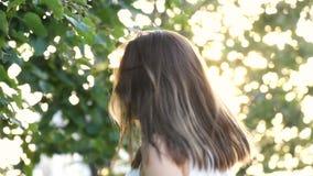 Torsioni sorridenti della ragazza cape e la sua mosca dei capelli via al rallentatore video d archivio