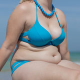 Torso of adult woman in swimsuit and beads, square composition. Girl on the beach. Torso of adult woman in blue swimsuit and beads, square composition stock photography