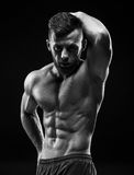 The torso of attractive male body builder on black background. Stock Photo