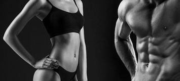 The torso of attractive male and female bodys on black background. Stock Photos
