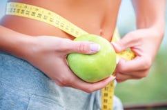 Torso av en ung kvinna med ett äpple och en meter royaltyfri bild