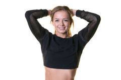 Torso of a blonde woman in black crop top. A beautiful young blonde woman in a black crop top with her hands behind her neck and isolated on a white background Stock Image