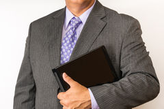 Torso of a business man wearing a suit. Elegant business person wearing a neat suit and tie holding a laptop Royalty Free Stock Photography