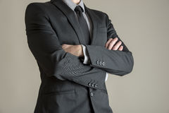 Torso of a businessman standing with folded arms. In a classic black suit, depicting confidence and authority stock photos