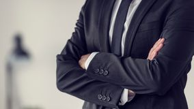 Torso of a businessman standing with folded arms. In a classic black suit, toned retro effect Stock Photo